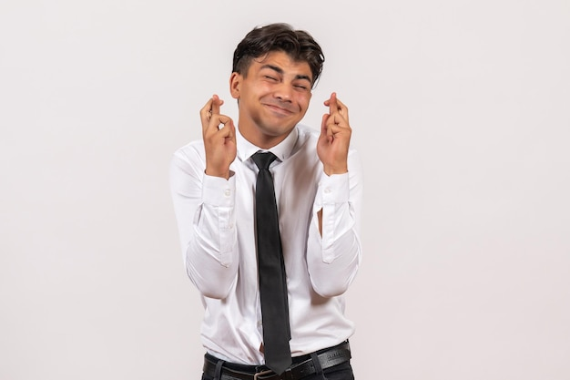 Front view male office worker crossing his fingers on white wall work business male job