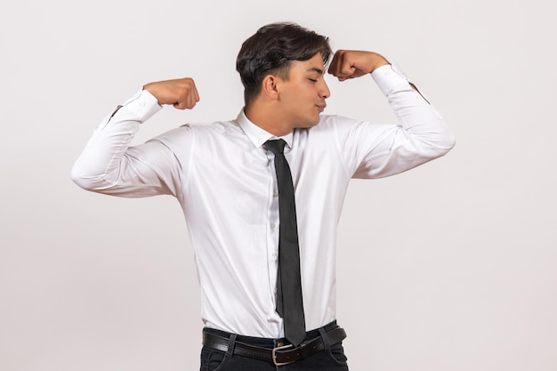 Front view male office worker flexing on white wall human office work job