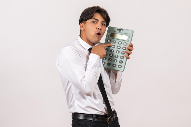 Front view male office worker holding calculator on a white wall work human job male