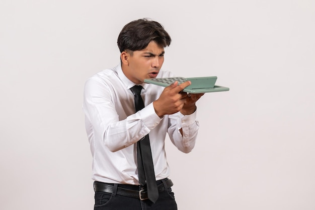 Front view male office worker holding calculator on white wall work office human job