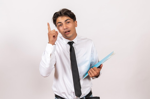Front view male office worker holding documents on white wall male business work job