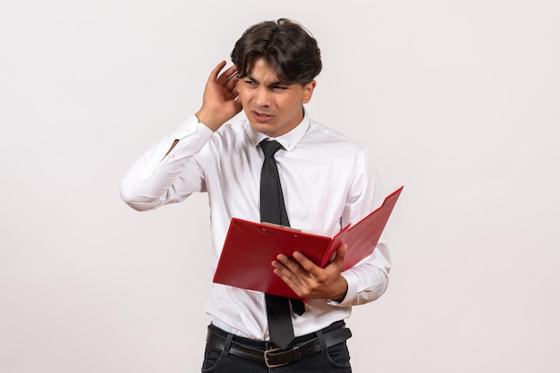 Front view male office worker holding red file on a white desk work office human job