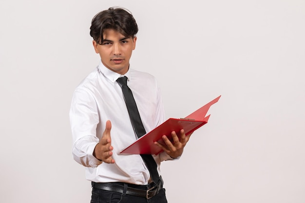 Front view male office worker holding red file on a white wall office work human job