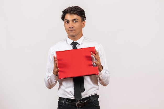 Front view male office worker holding red file on white wall office work job human