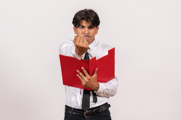 Front view male office worker holding red file on the white wall work office human job