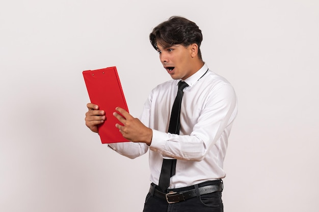 Front view male office worker holding red file on white wall work office human job