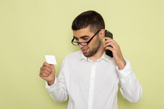 Vista frontale dell'impiegato maschio in carta bianca della tenuta della camicia e parlando al telefono sulla parete verde