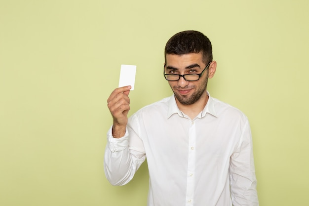 Front view of male office worker in white shirt holding card with smile on the light-green wall
