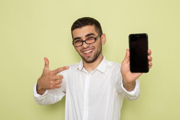 Vista frontale del lavoratore di ufficio maschio in camicia bianca che tiene il suo telefono sorridente sulla parete verde