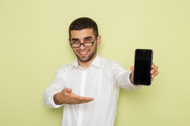 Vista frontale del lavoratore di ufficio maschio in camicia bianca che tiene il suo telefono con il sorriso sulla parete verde