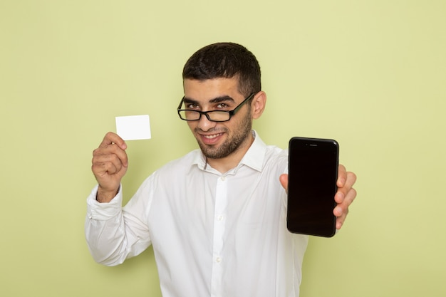 Front view of male office worker in white shirt holding smartphone and card on light-green wall