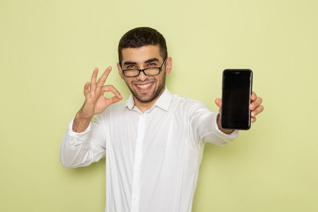Front view of male office worker in white shirt holding smartphone on the light-green wall