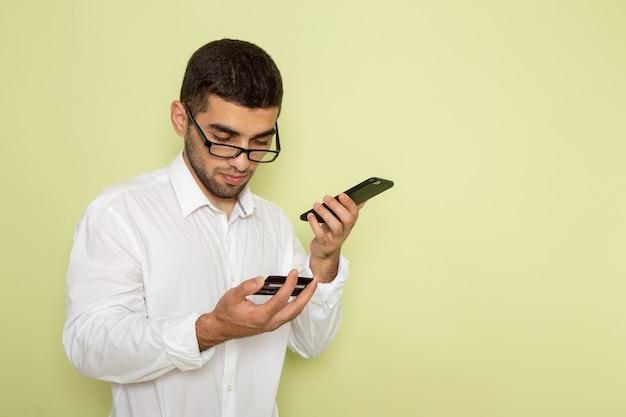 Vista frontale del lavoratore di ufficio maschio in camicia bianca che tiene e utilizza il suo telefono sulla parete verde chiaro