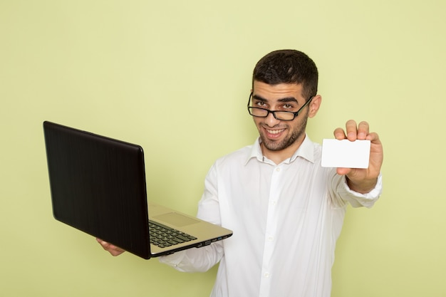 Front view of male office worker in white shirt holding white card and laptop on the green wall