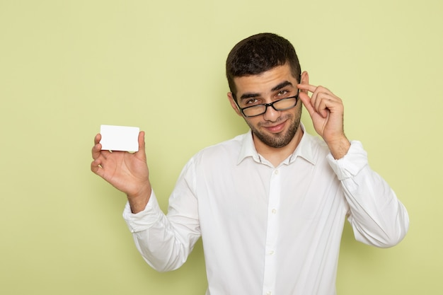 Front view of male office worker in white shirt holding white plastic card on light-green wall