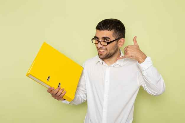 Front view of male office worker in white shirt holding yellow files smiling on the green wall