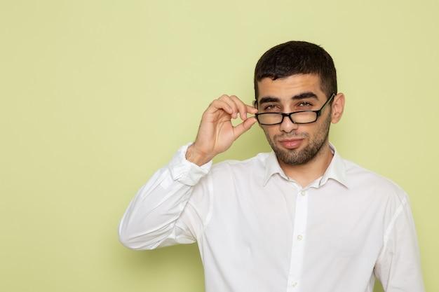 Vista frontale dell'impiegato maschio in camicia bianca sulla parete verde chiaro