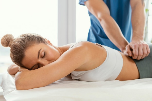 Front view of male osteopathic therapist checking female patient's lower back spine
