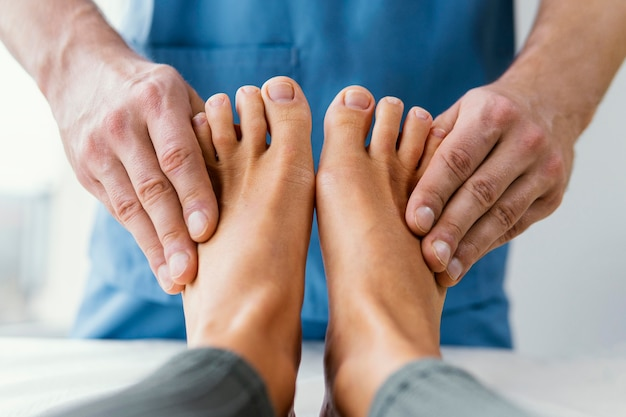 Front view of male osteopathic therapist checking female patient's toes