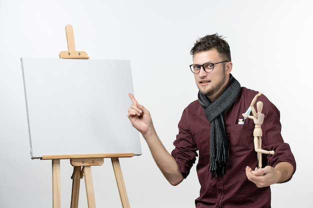 Front view male painter along with easel holding human figure on the white wall