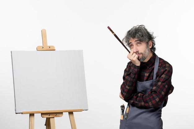 흰 벽에 페인트 붓을 들고 이젤과 함께 전면보기 남성 화가