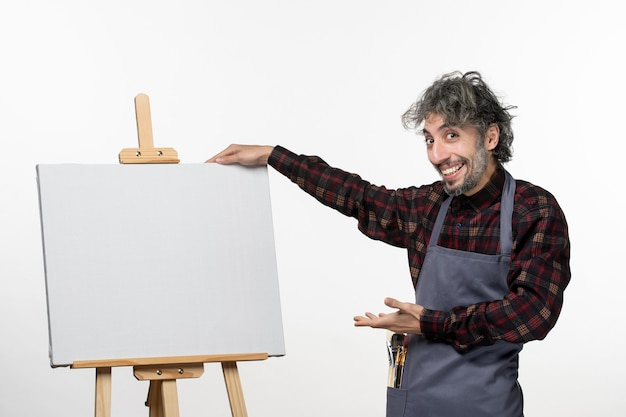 Front view male painter along with easel on white wall