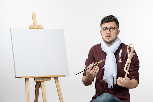 Front view male painter drawing on easel with paint brush on white wall