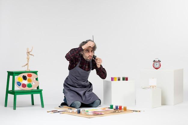 Vista frontale pittore maschio che disegna immagini con vernici su bianco lavoro artista colore disegnare pittura immagine artistica