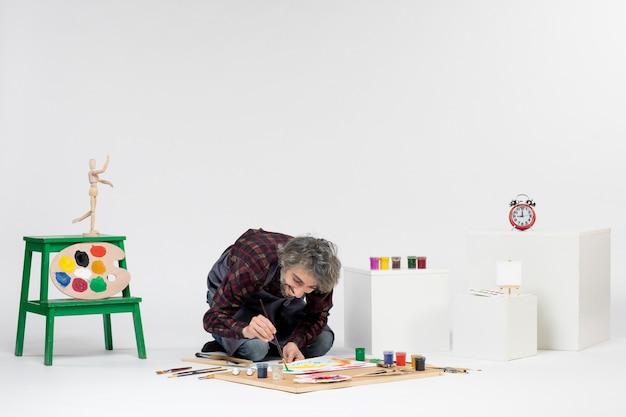 Vista frontale pittore maschio che disegna immagini con vernici su bianco lavoro immagine artista colore disegnare pittura arte