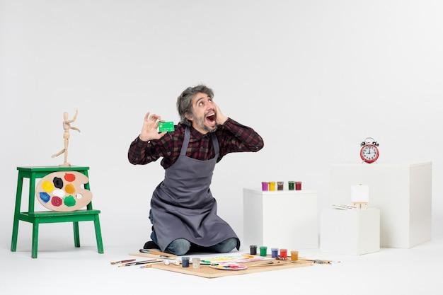 흰색 배경에 은행 카드를 들고 있는 전면 보기 남성 화가 작업 컬러 그림 예술 그림 예술가 돈 페인트
