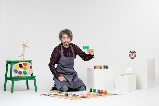 흰색 배경에 은행 카드를 들고 있는 전면 보기 남성 화가 컬러 그림 미술가 그림 작업