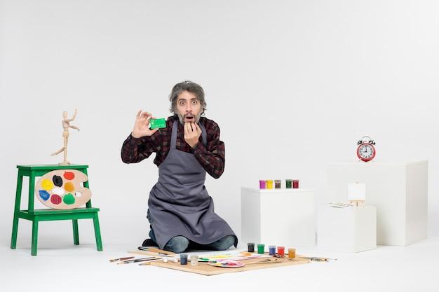 흰색 배경에 은행 카드를 들고 있는 전면 보기 남성 화가 그림 컬러 아티스트 돈 작업 페인트 아트 사진