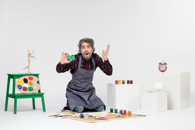Vista frontale pittore maschio in possesso di carta di credito su sfondo bianco lavoro immagine a colori arte pittura artista soldi vernici