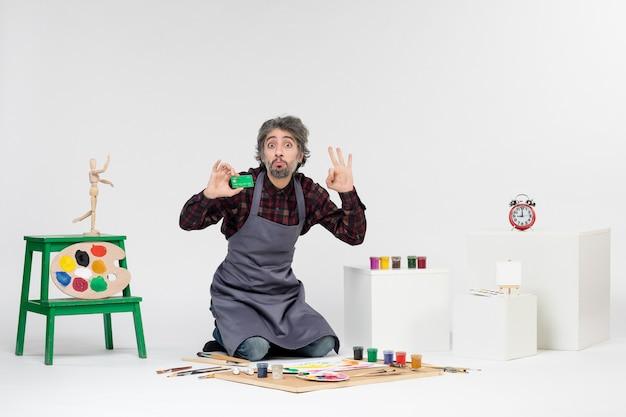 Vista frontale pittore maschio in possesso di carta di credito verde e contando su sfondo bianco immagine pittura arte colore artista lavoro soldi vernice