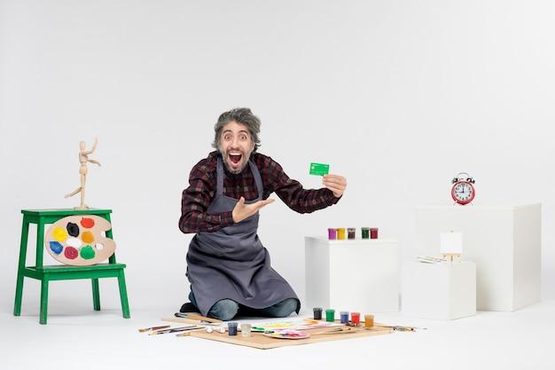 전면 보기 남성 화가 흰색 배경에 녹색 은행 카드를 들고 예술 컬러 그림 그림 돈 예술가 직업