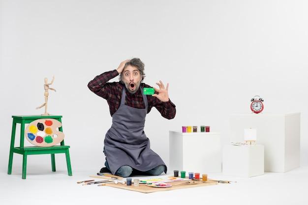 흰색 배경에 녹색 은행 카드를 들고 있는 전면 보기 남성 화가 돈 그림 컬러 그림 아티스트 작업 예술