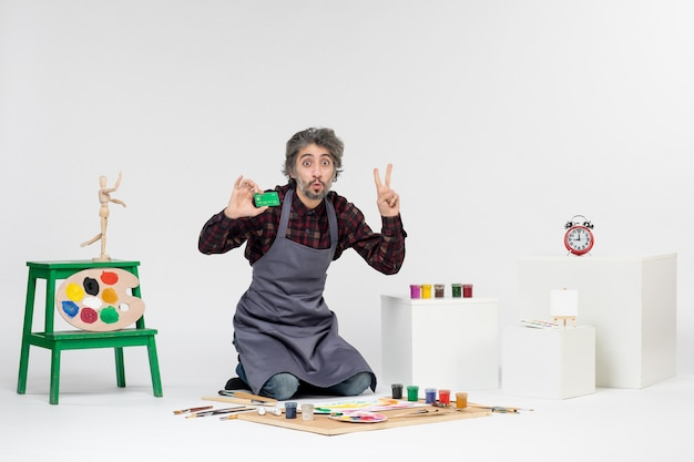 흰색 배경에 녹색 은행 카드를 들고 있는 전면 보기 남성 화가 그림 예술 그림 컬러 아티스트 작업 돈 페인트