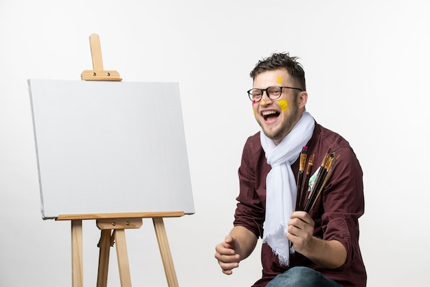 Front view male painter holding paint brushes on white wall