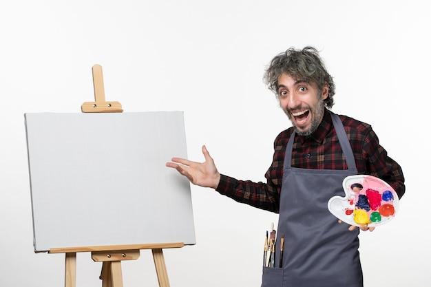 흰 벽에 페인트를 들고 전면보기 남성 화가