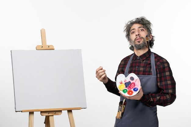 Front view male painter holding paints and preparing to draw on a white wall