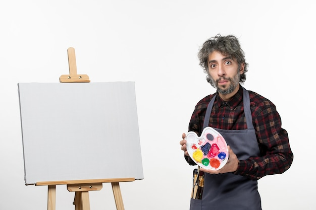 Front view male painter holding paints and preparing to draw on the white wall