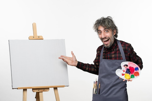 Front view male painter holding paints on white wall