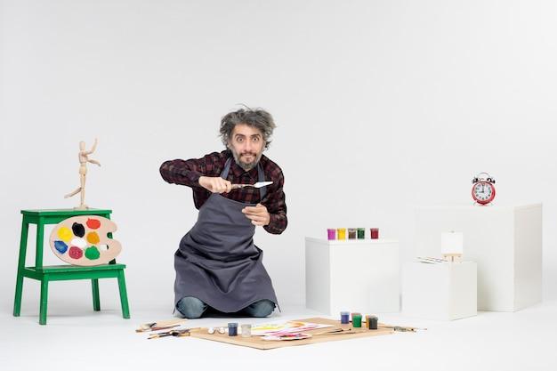 Vista frontale pittore maschio all'interno della stanza piena di vernici e nappe per disegnare sullo sfondo bianco artista che disegna la pittura a colori dell'immagine