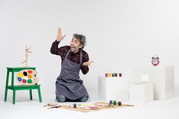 Vista frontale pittore maschio all'interno della stanza piena di vernici e nappe per disegnare su sfondo bianco artista che disegna pittura immagine artistica