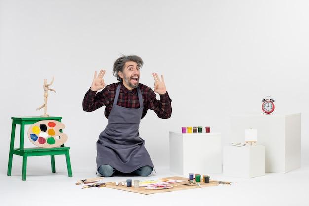 Vista frontale pittore maschio all'interno della stanza piena di vernici e nappe per disegnare su sfondo bianco artista disegno pittura immagine a colori arte