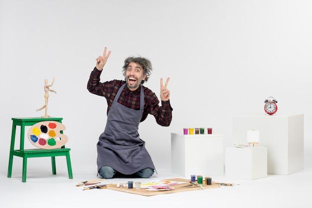 Vista frontale pittore maschio all'interno della stanza piena di vernici e nappe per disegnare su sfondo bianco disegno a colori pittura immagine artistica