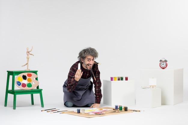 흰색 배경에 그리기 위한 페인트와 페인트 브러시가 있는 방 안에 있는 전면 보기 남성 화가는 남자 예술가 그림 예술 컬러 그림을 그립니다.