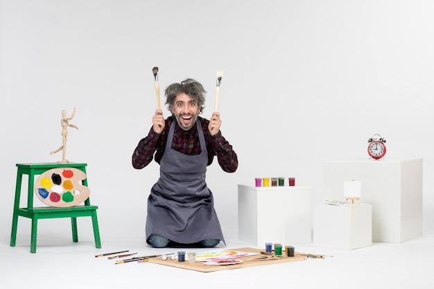 흰색 배경에 그림을 그리기 위한 페인트와 페인트 브러시가 있는 방 안에 있는 전면 보기 남성 화가