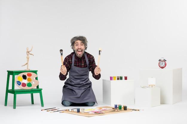 흰색 배경에 페인트와 페인트 브러시가 있는 방 안에 있는 전면 보기 남성 화가는 작업 예술을 그립니다.