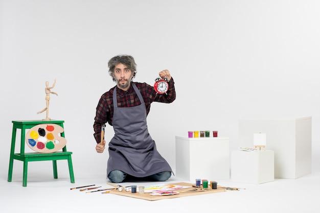 흰색 배경에 페인트와 페인트 브러시가 있는 방 안에 있는 전면 보기 남성 화가는 예술 색상 그림 작업 그림 예술가를 그립니다.